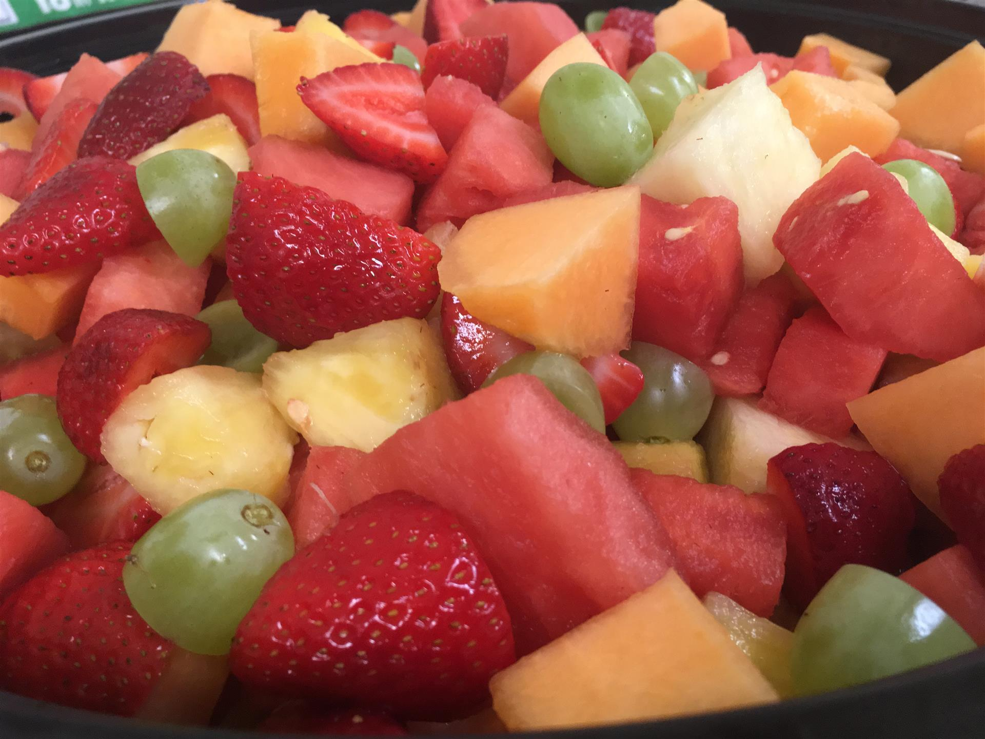 fresh fruit bowl with cantaloupe, watermelon, strawberries, grapes and pineapple