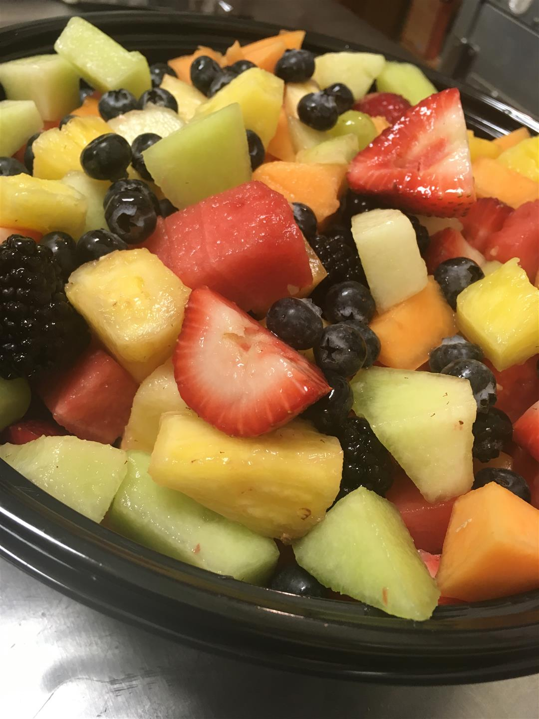fresh fruit bowl with honeydew, pineapple, strawberries, blueberries, and blackberries