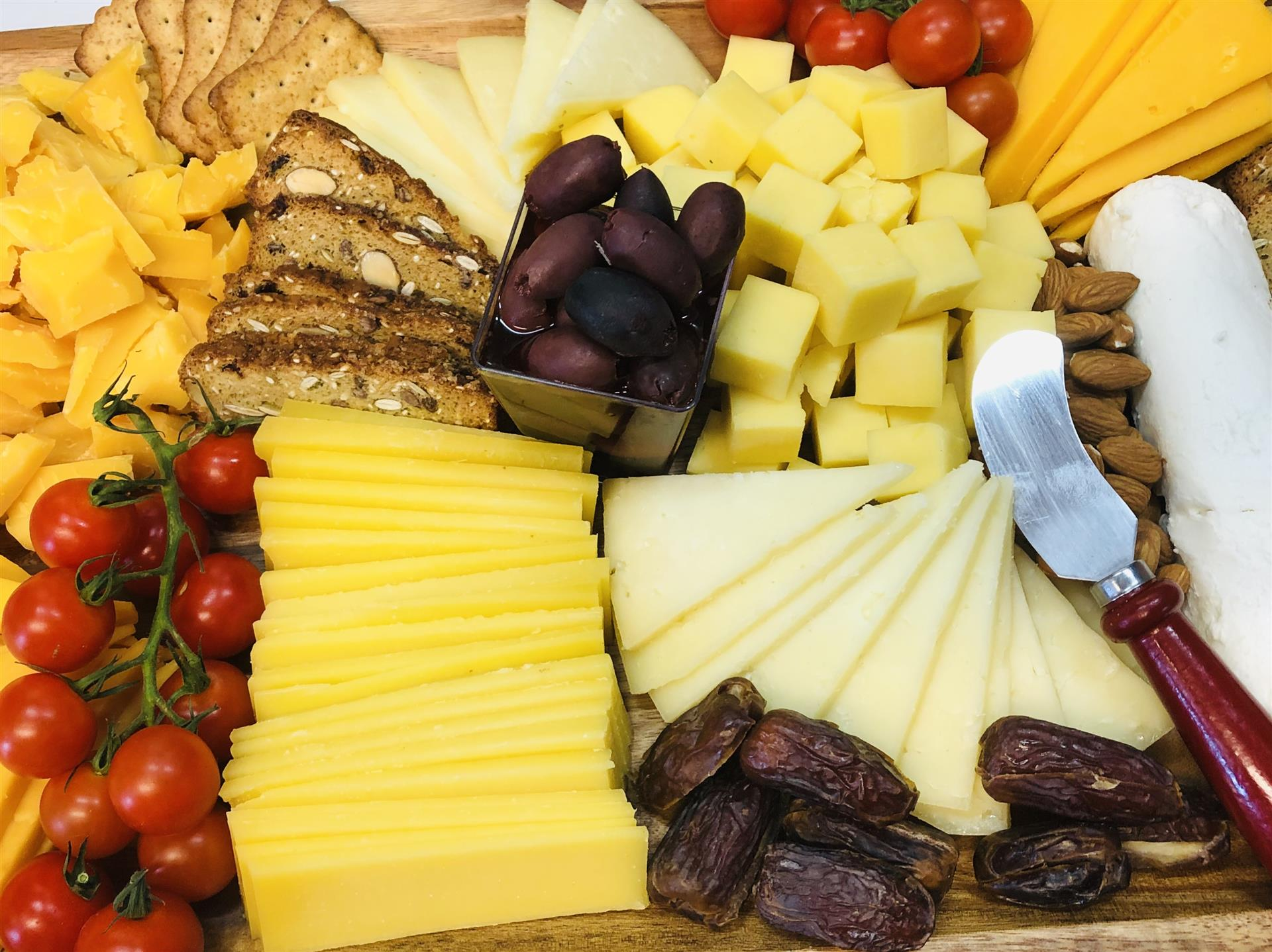 imported cheese platter with assorted cheeses, dates, cherry tomatoes and rustic bread