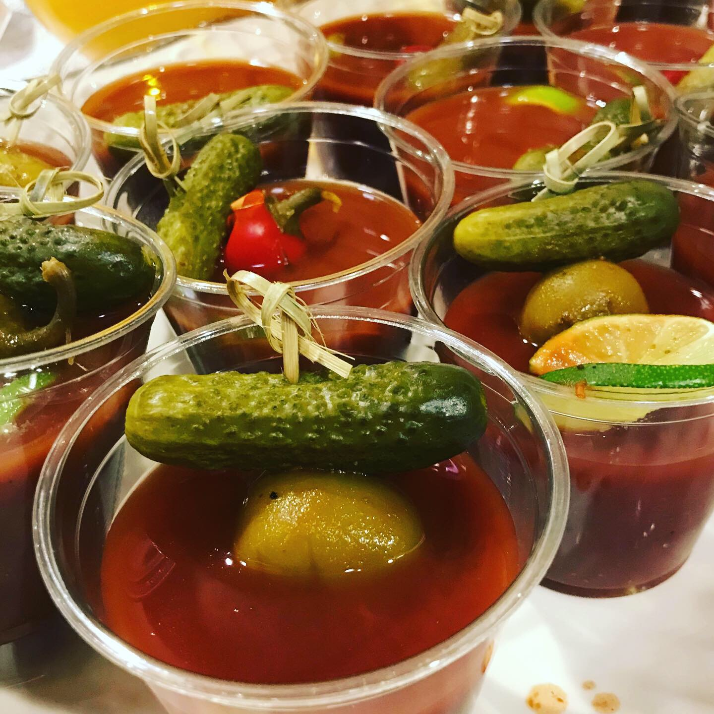bloody mary mocktail closeup with olive and gerkin pickle garnish