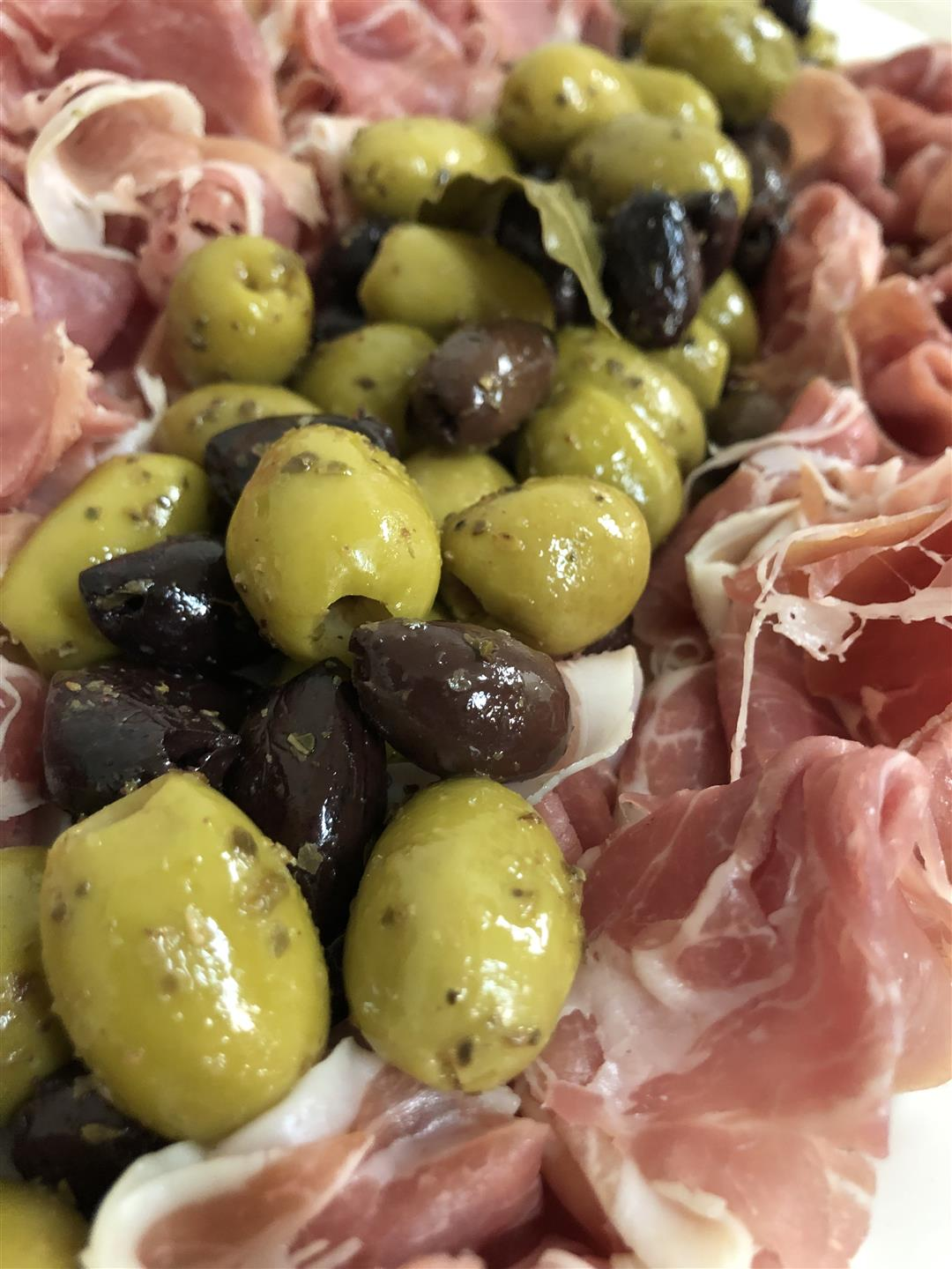 arrangement of marinated olives and proscuitto