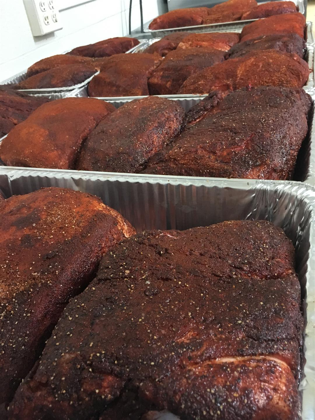 multiple trays of seasoned smoked pork butts