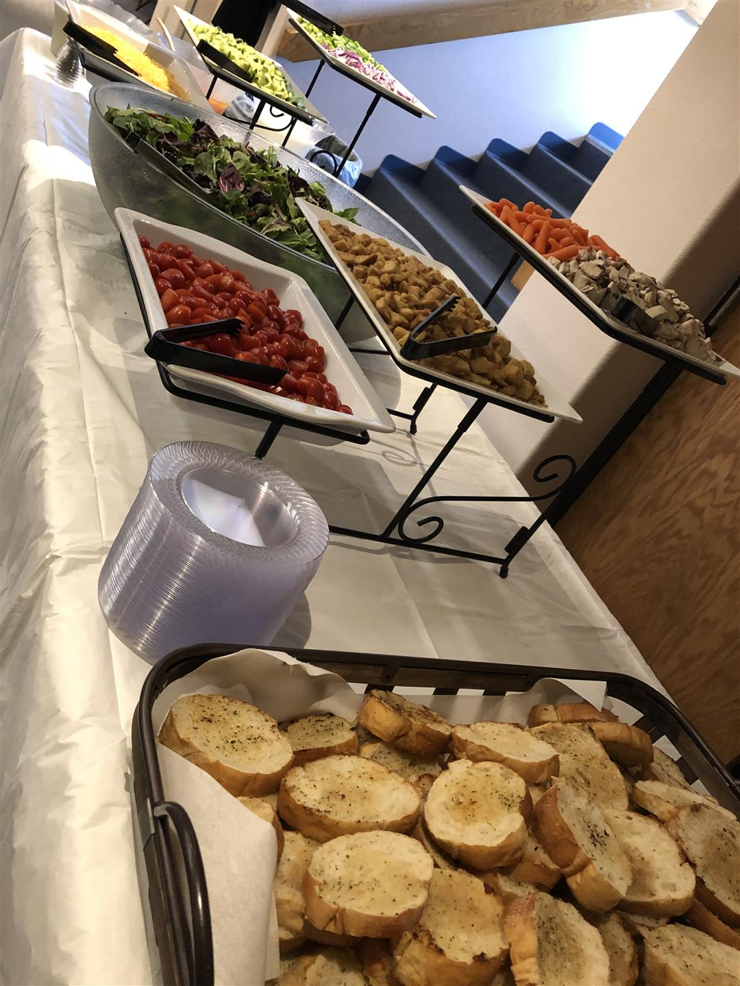 salad bar with assorted toppings and sliced italian bread