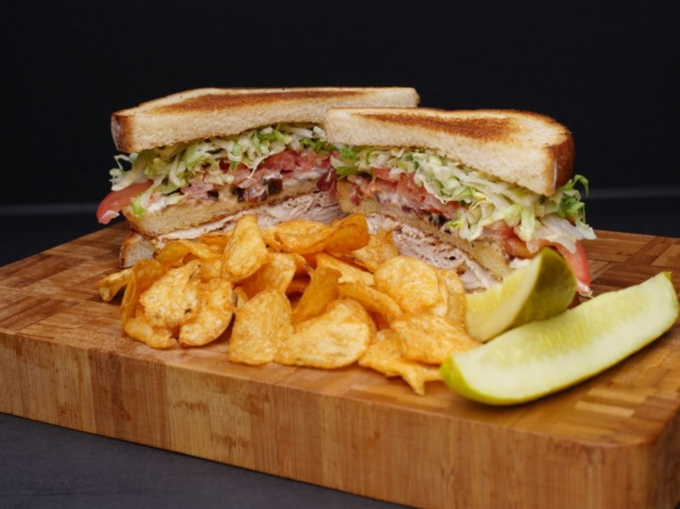 a sandwich with meat, lettuce, tomato, and onions with chips and pickles on the side