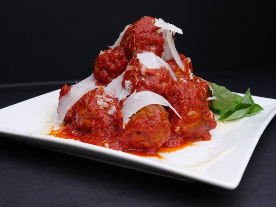 meatballs with red sauce and shaved cheese on top