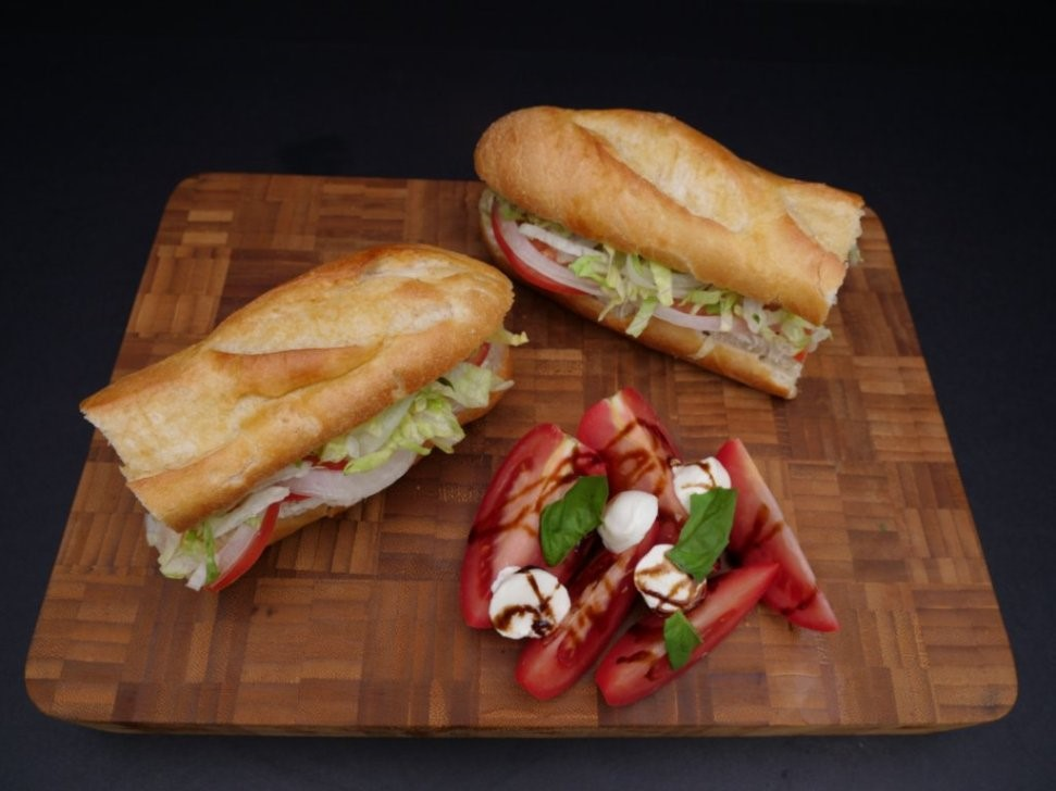 sandwich with meat, lettuce, tomato, ontions and a side of tomato and mozzarella