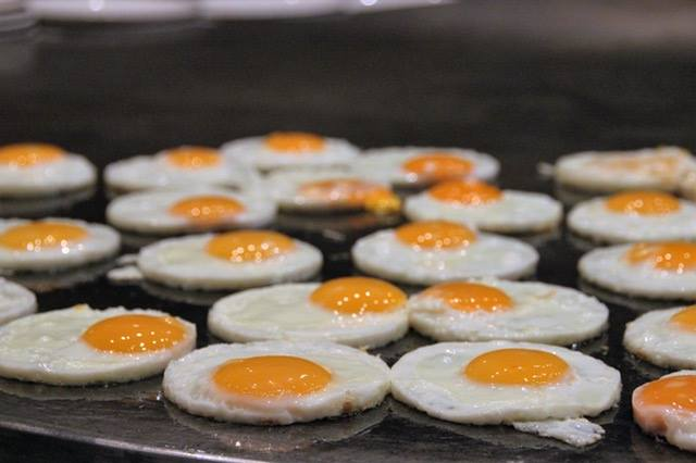 a dozen fried eggs being cooked on a stove top