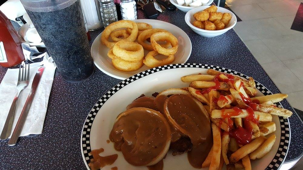 burger with gravy and onions with a side of french fries and onion rings
