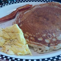 large lancakes with a side of scrambled eggs and bacon