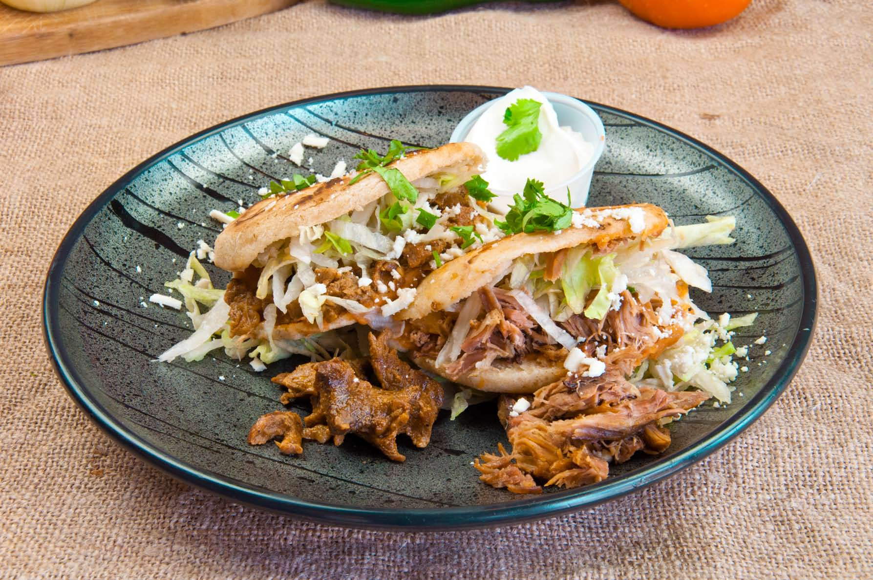 Two Carnitas Tacos Topped with shredded lettuce and cheese