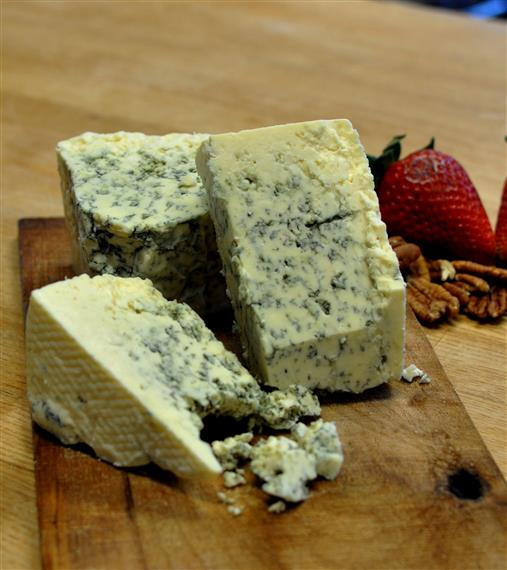 blocks of bleu cheese on a wooden plate