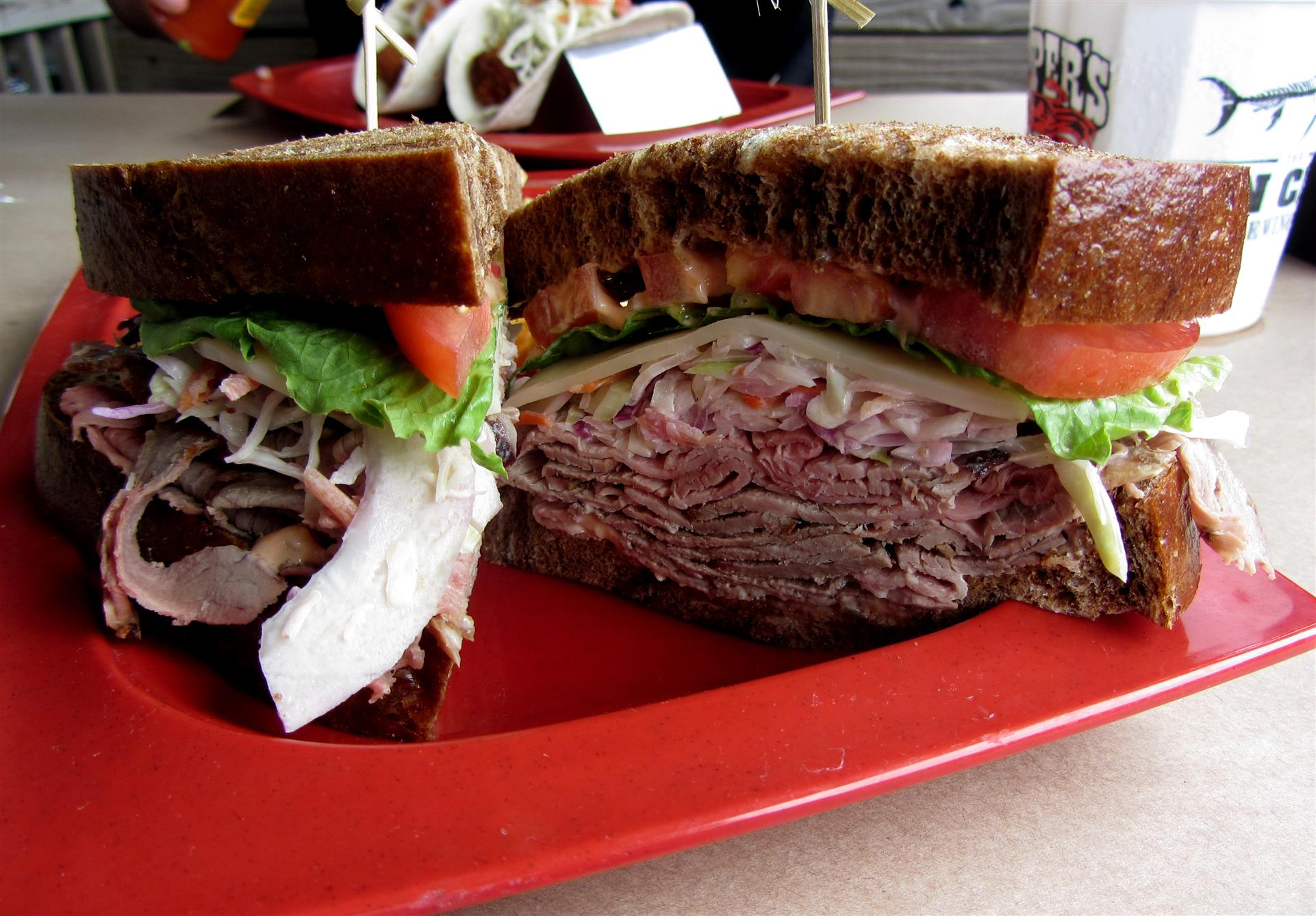 A cold cut sandwich which includes ham, roast beef, swiss cheese, salami, lettuce and tomato