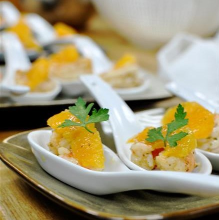 Service spoons full of grilled shrimp topped with mandarin oranges for a catering event