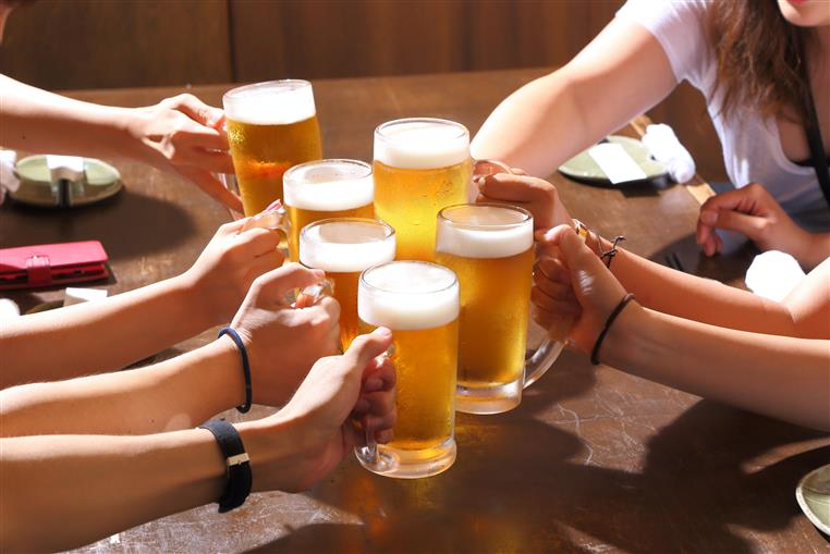 six mugs of beer held being touched against each other