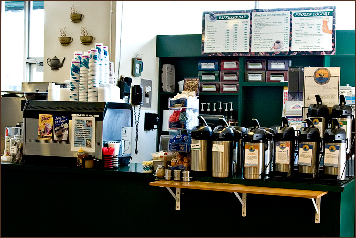 Station of coffee dispensers, cups, menus on wall.