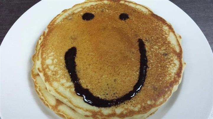 A smiling face is drawn with chocolate syrup over pancakes