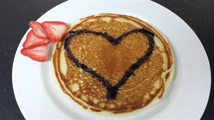 A heart is drawn with chocolate syrup over pancakes