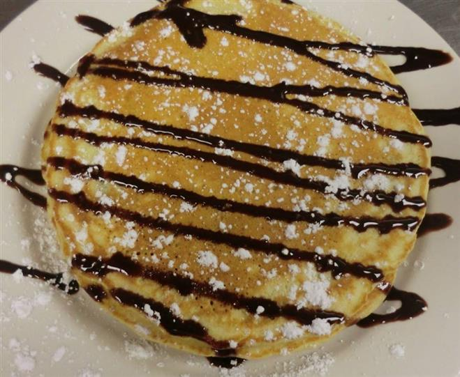 Pancakes topped with chocolate syrup and powdered sugar