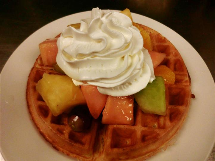 A Belgian waffle topped with pieces of fresh fruits and whipped cream