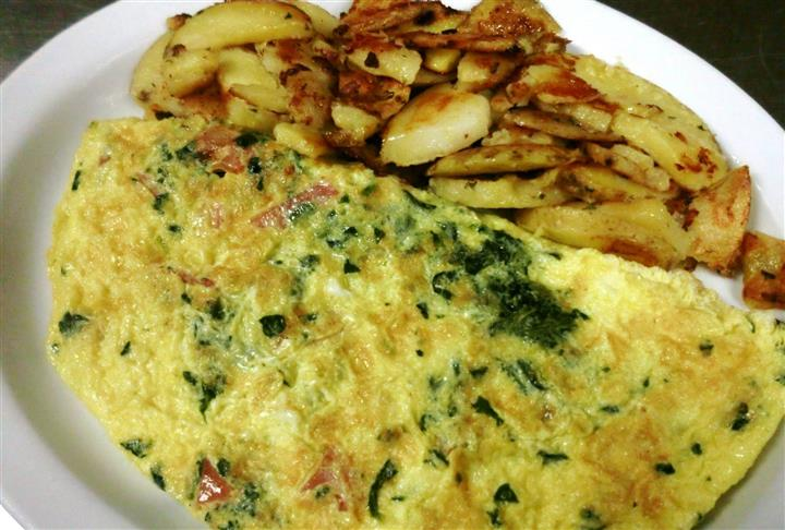 A spinach omelet served with potatoes