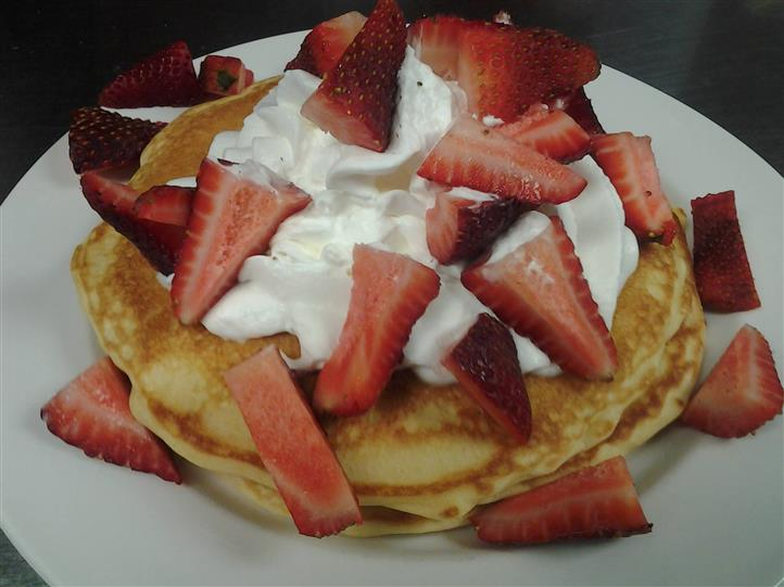Three pancakes topped with whipped cream and strawberries