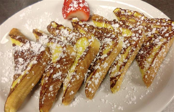 A dish of French toasts topped with powdered sugar