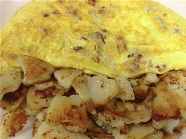 An bacon omelet served with potatoes