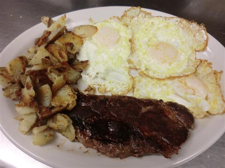 A dish of three fried eggs, a piece of beef and potatoes