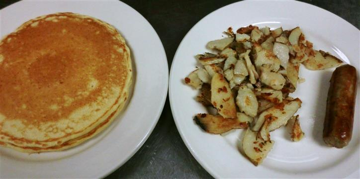 A dish of pancakes and a dish of a sausage link with potatoes