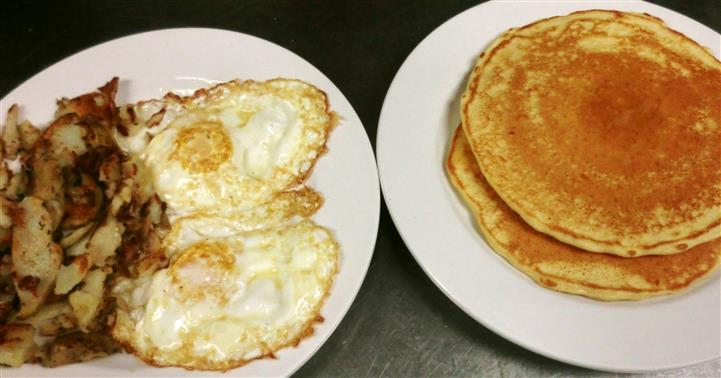 A dish of two fried eggs and a dish of pancakes
