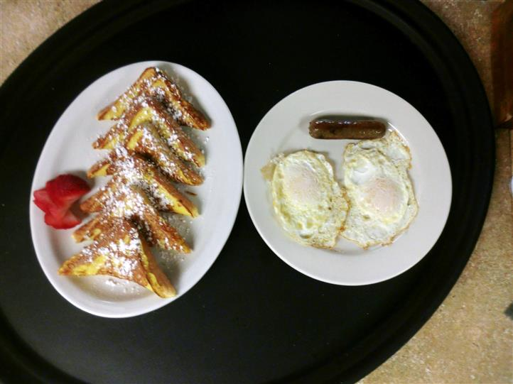 A platter of French toasts and a dish of two fried eggs and a sausage link