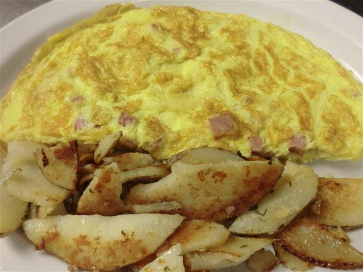A bacon omelet served with sliced potatoes