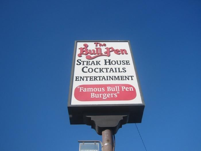 Sign outside restaurant. The Bull Pen. Steak house, cocktails, entertainment. Famous bull pen burgers.