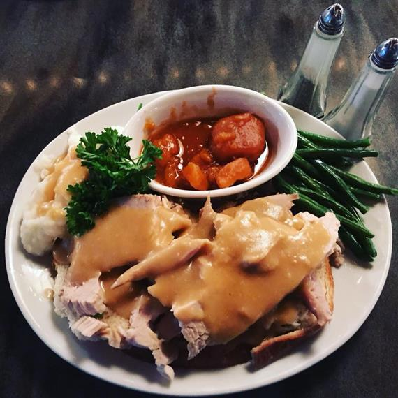 Turkey with gravy, mashed potatoes, and vegetable.