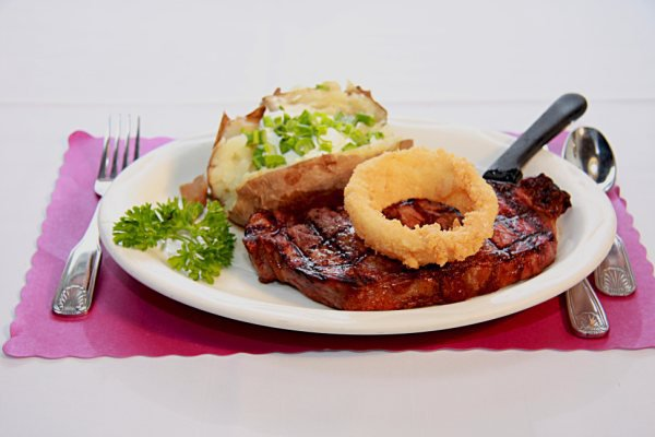 Steak, baked potato with sour cream and chives, and onion ring.