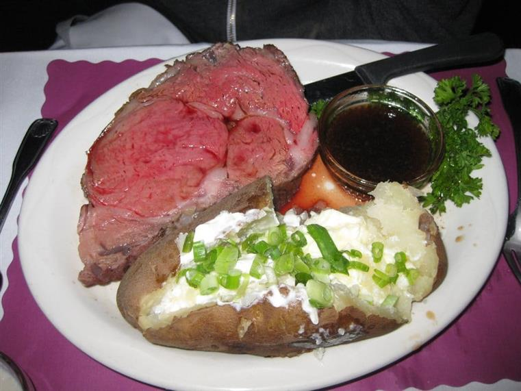 Prime rib with side of au jus and baked potato