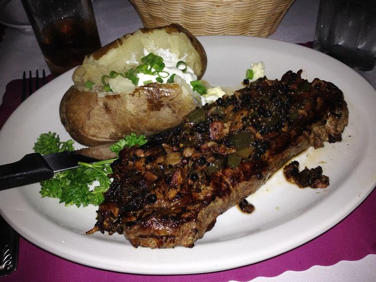 Steak and baked potato with sour cream and chives