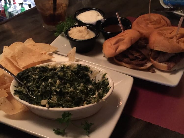 Creamed spinach and tortilla chips in front of three hamburgers