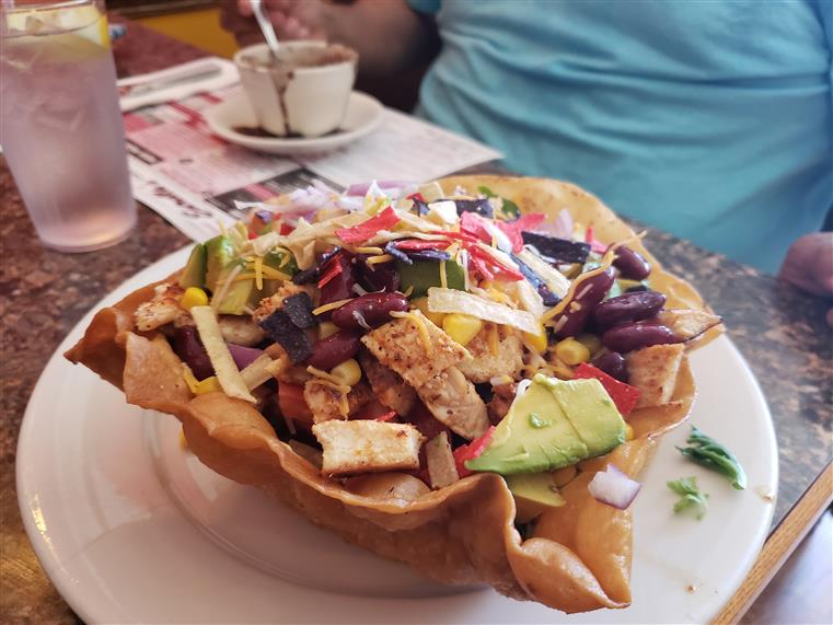 side view of the Chicken Avocado Taco Salad which includes Lettuce, tomato, cucumbers, corn, beans, cilantro & pepper jack cheese, Served in a hard shell tortilla with sour cream & guacamole