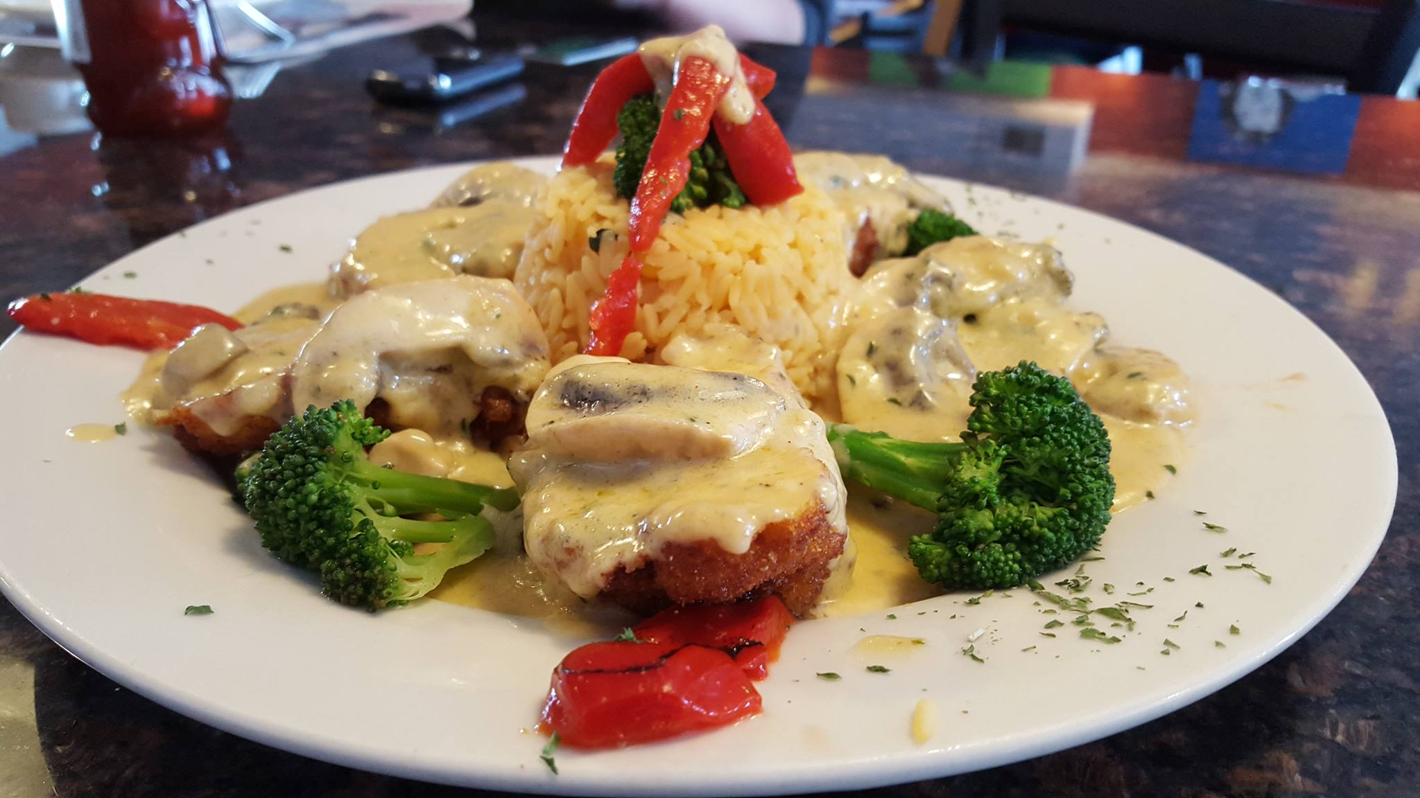 breaded chicken with roasted peppers, broccoli and mushrooms in a white cream sauce served with a side of rice