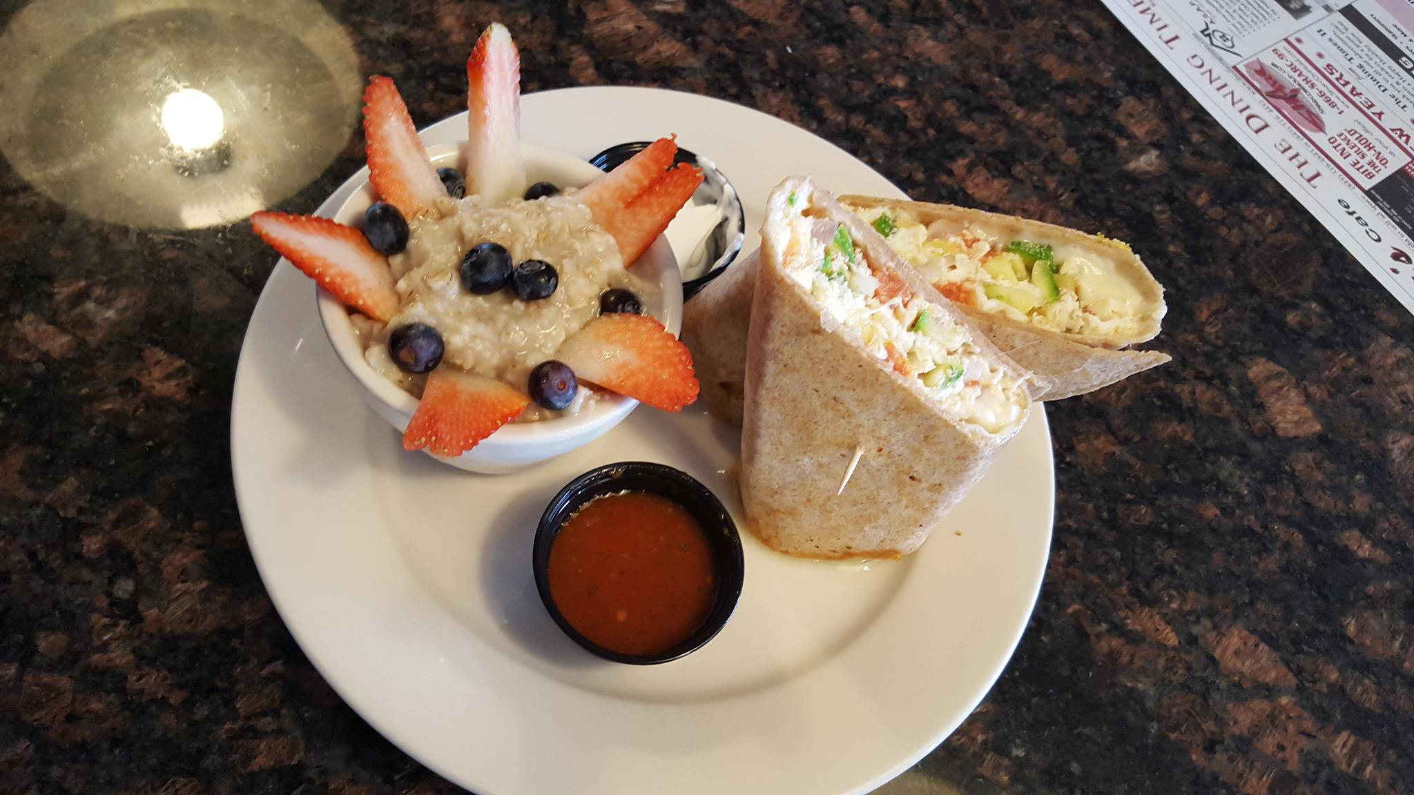 breakfast wrap with eggs and a fruit cup on the side.