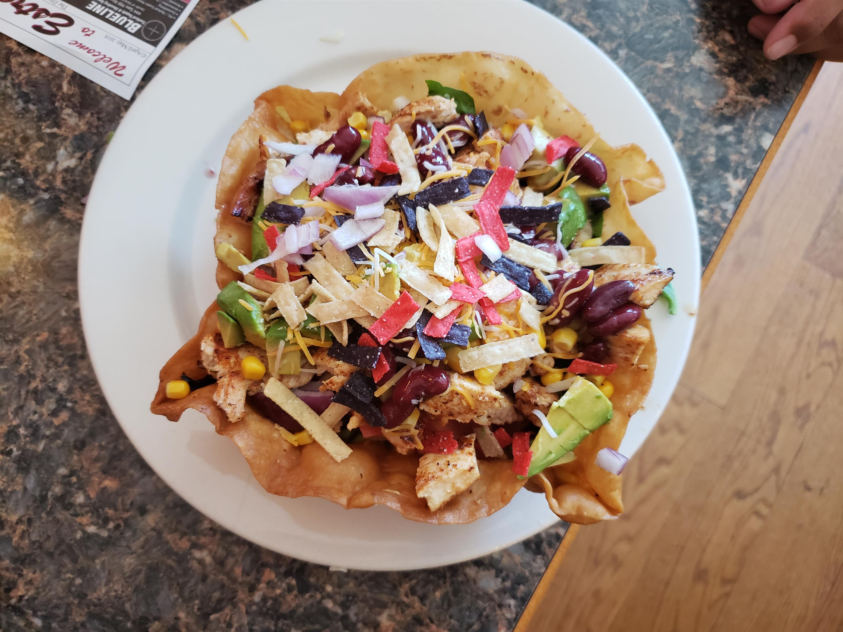 top view of the Chicken Avocado Taco Salad which includes Lettuce, tomato, cucumbers, corn, beans, cilantro & pepper jack cheese, Served in a hard shell tortilla with sour cream & guacamole
