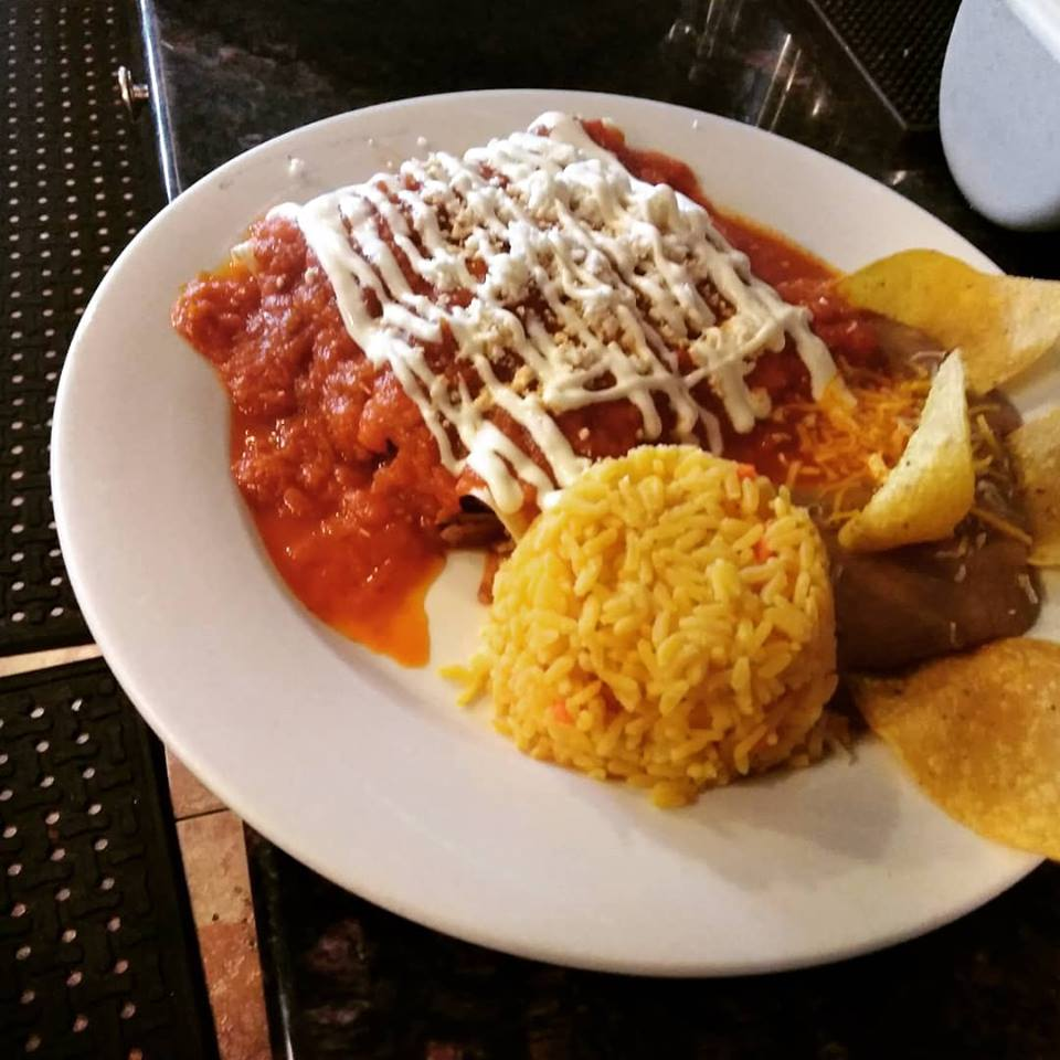 enchiladas with refried beans and rice with a side of tortilla chips