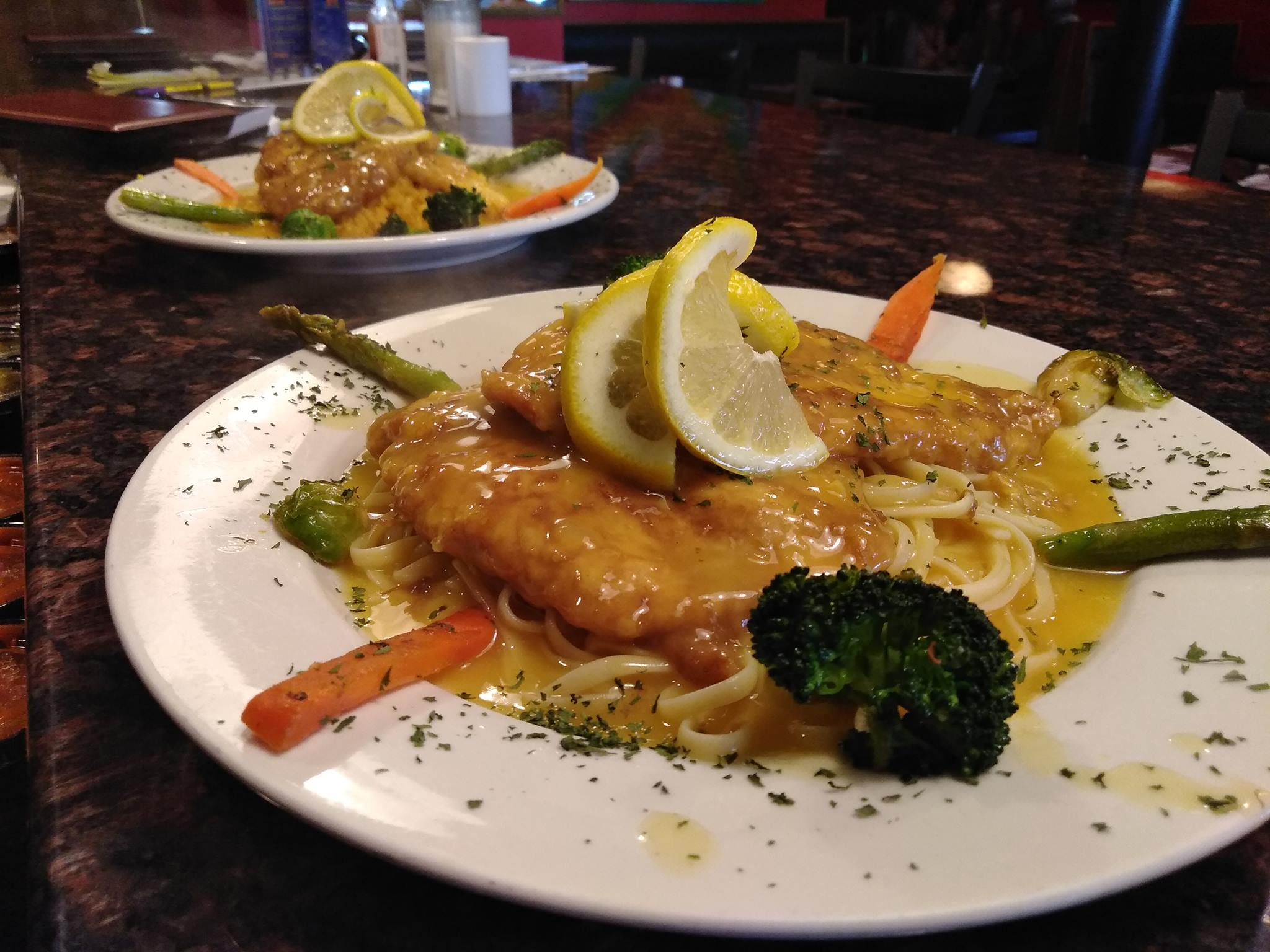 Chicken Francaise with pasta and sauteed vegetables and a lemon wedge