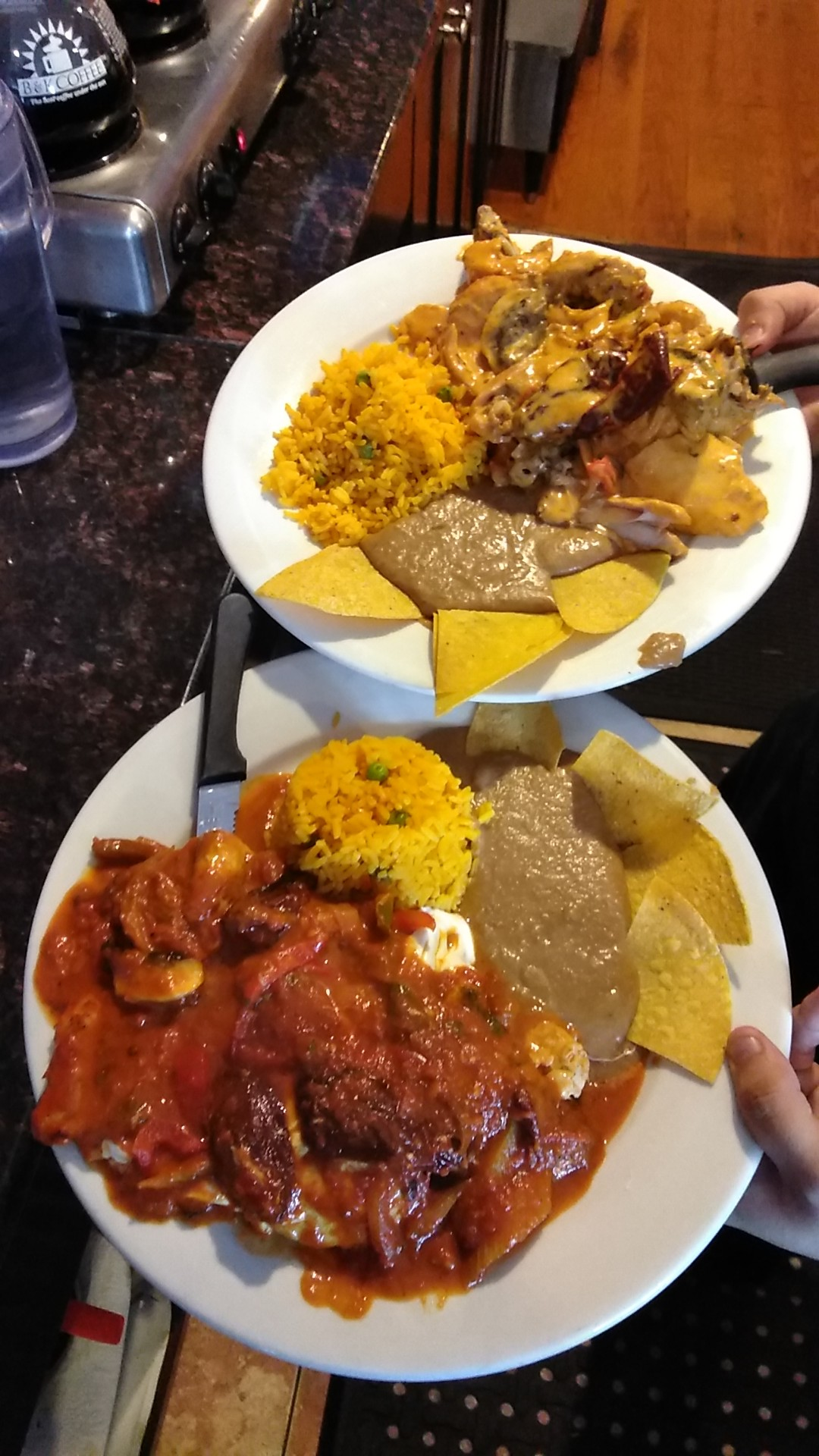 Two dishes with refried beans, rice and tortilla chips.