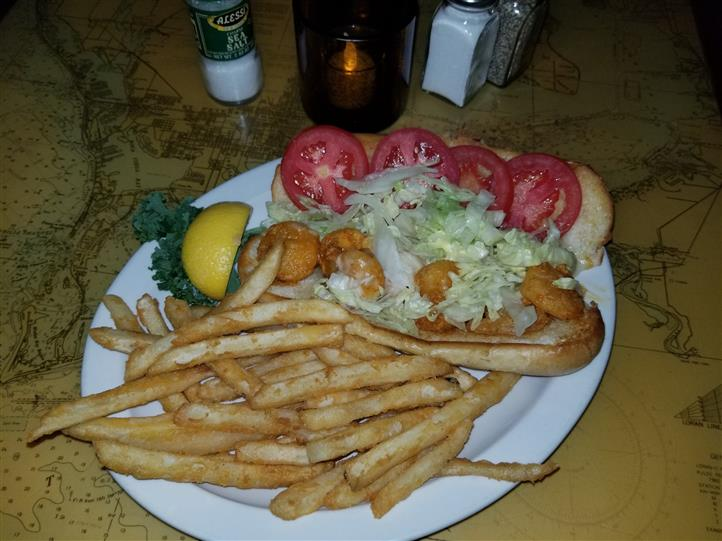 fried shrimp on a roll with tomatoes and lettuce with fries
