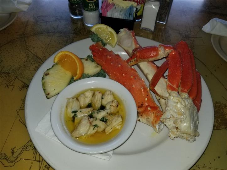crab legs with lemon wedge and vegetables