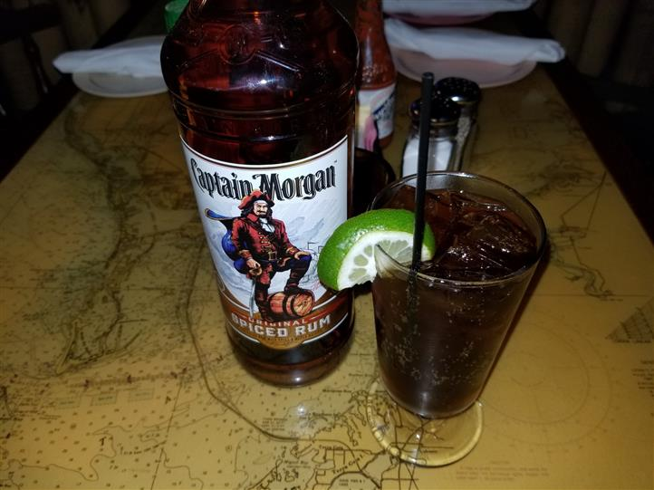 captain morgan spiked coke with lime wedge in a glass