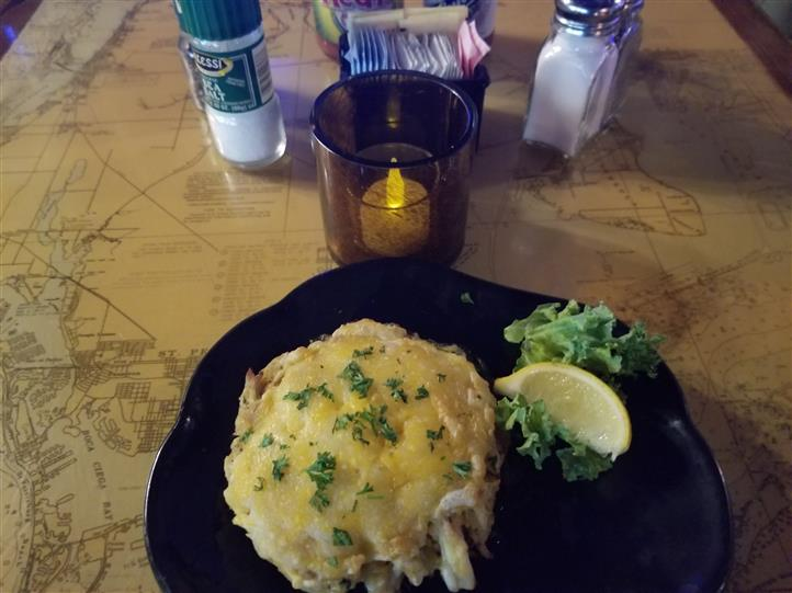 crab cake on a plate with lemon wedge