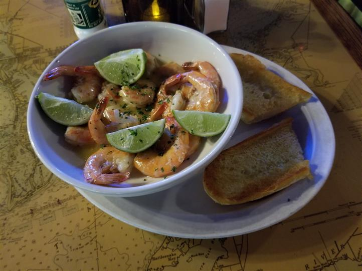 fresh shrimp in a bowl with lime wedges and garlic bread